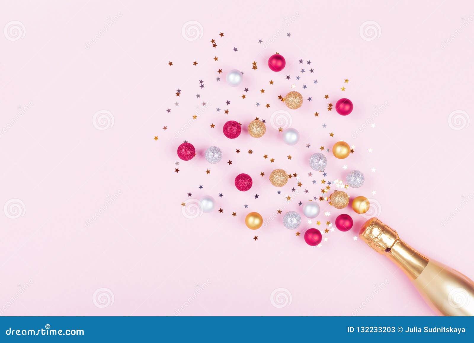 Bottiglia di Champagne con le stelle dei coriandoli e le palle di festa su fondo rosa pastello Reticolo di natale stile piano di
