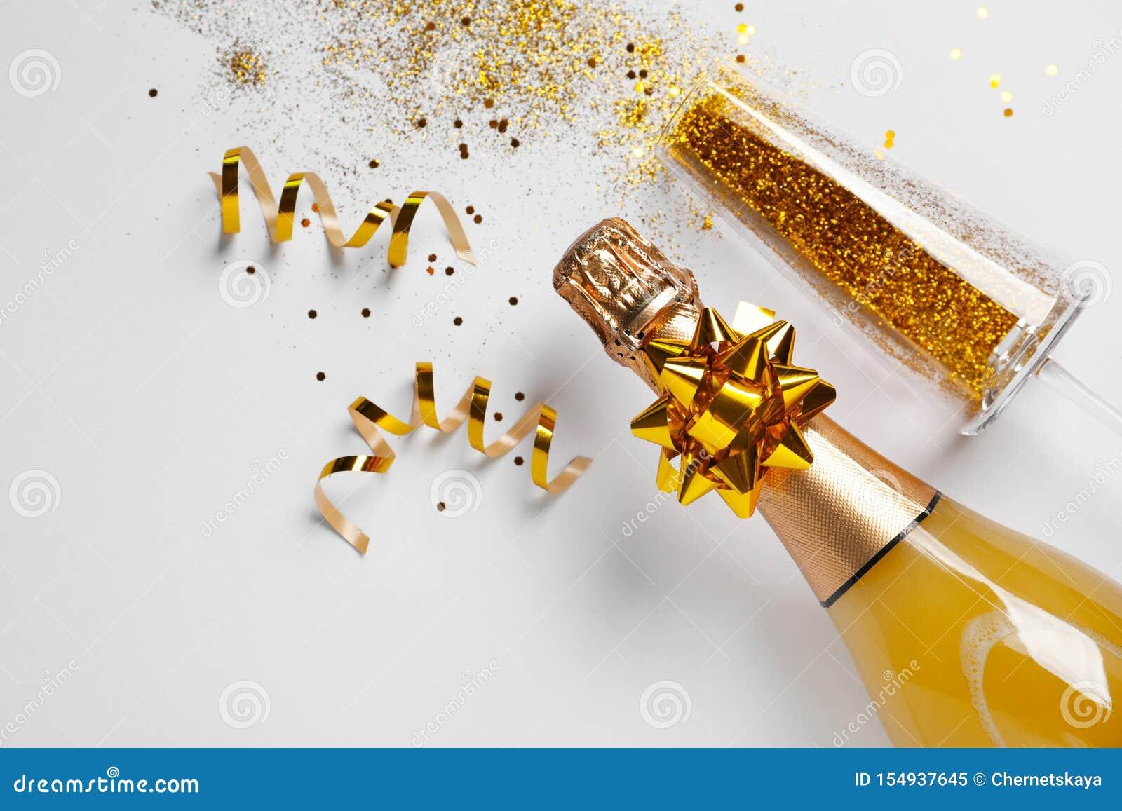 Bottiglia di champagne e di vetro con scintillio dell oro su fondo bianco, vista superiore hilarious