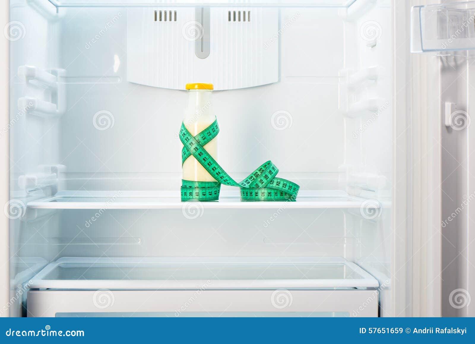 Bottiglia di vetro di yogurt con nastro adesivo di misurazione sullo scaffale del frigorifero vuoto aperto