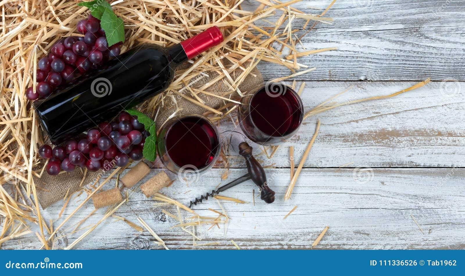Anniversario Ufficio : Bottiglia di vino rosso più i bicchieri sopra paglia e l ufficio
