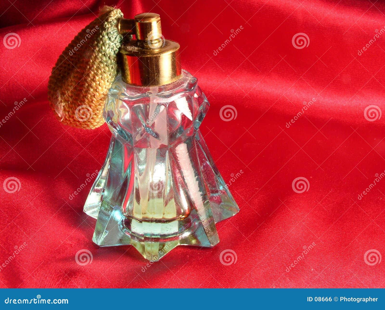 Bottiglia rossa di profumo e del raso