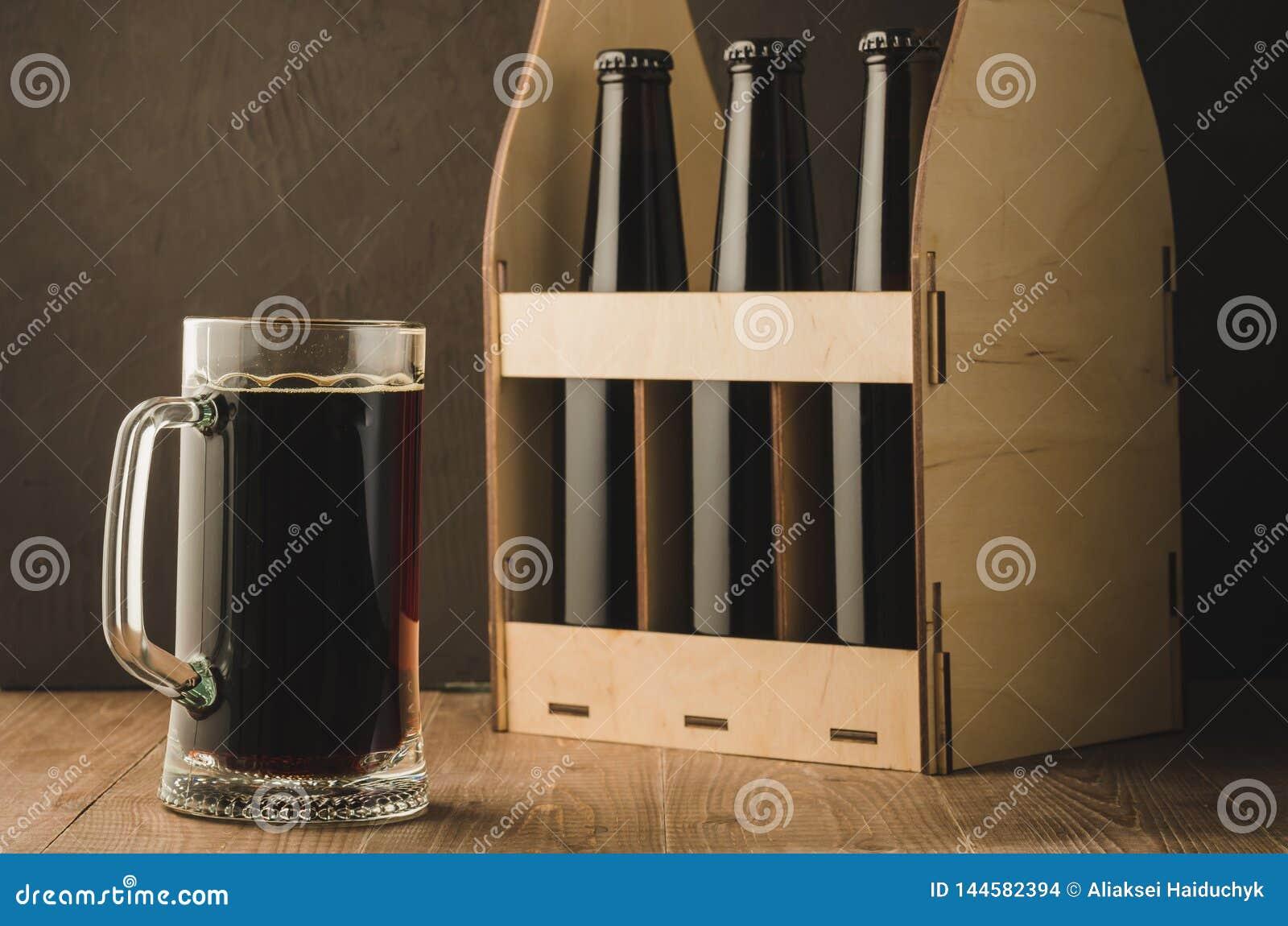 Bottiglie di birra caso e bottiglie caso e tazza di /beer della tazza su una tavola di legno Fuoco selettivo