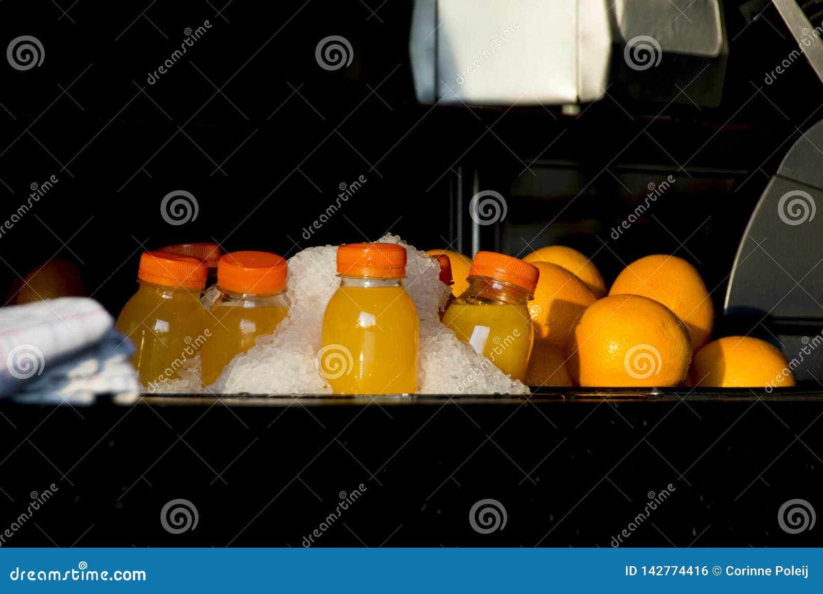 Bottiglie di plastica di succo d arancia con frutta in ghiaccio