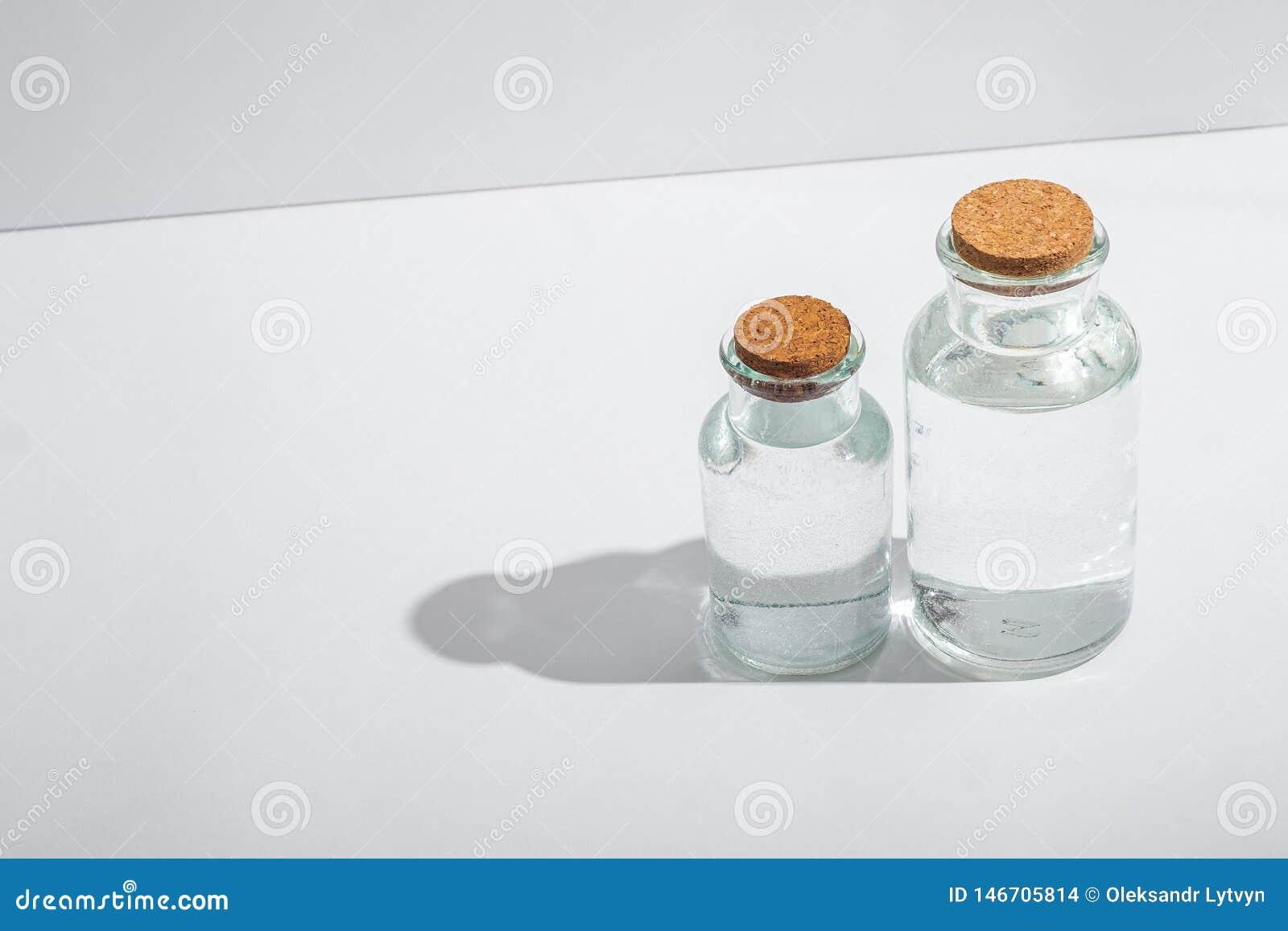 Bottiglie di vetro con i coperchi del sughero su un fondo bianco