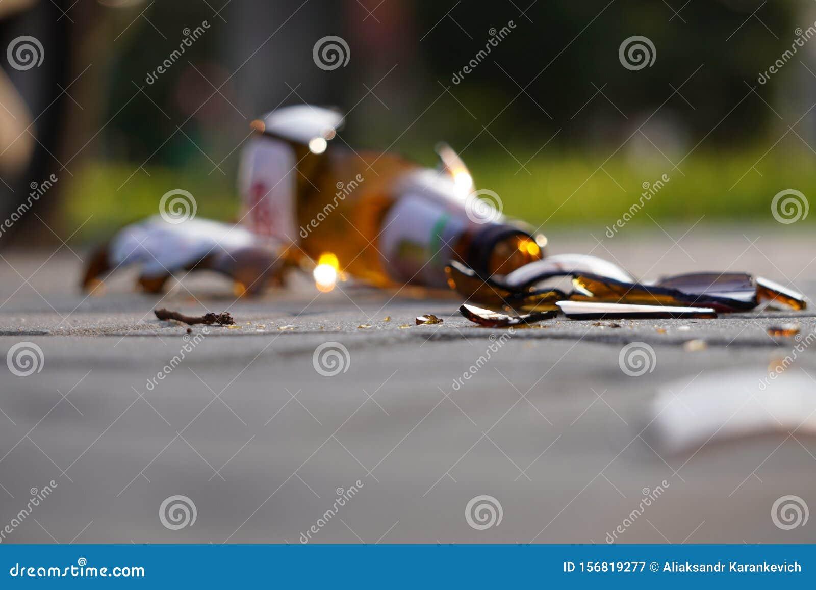 Bottle of beer, soda or drugs from dark glass is broken. Shattered beer bottle on ground in sunset light. Fragments of glass on