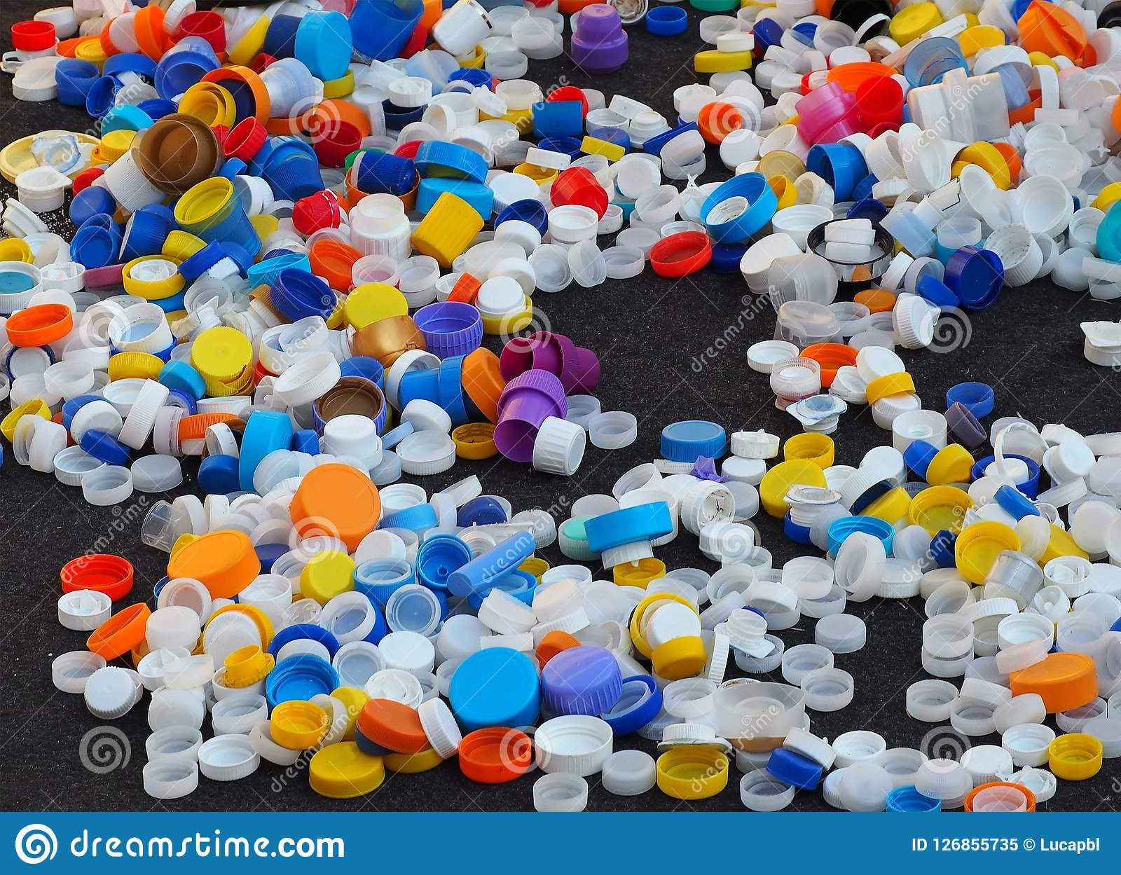 Bottle Caps And Other Types Of Plastic Caps Scattered On A Black