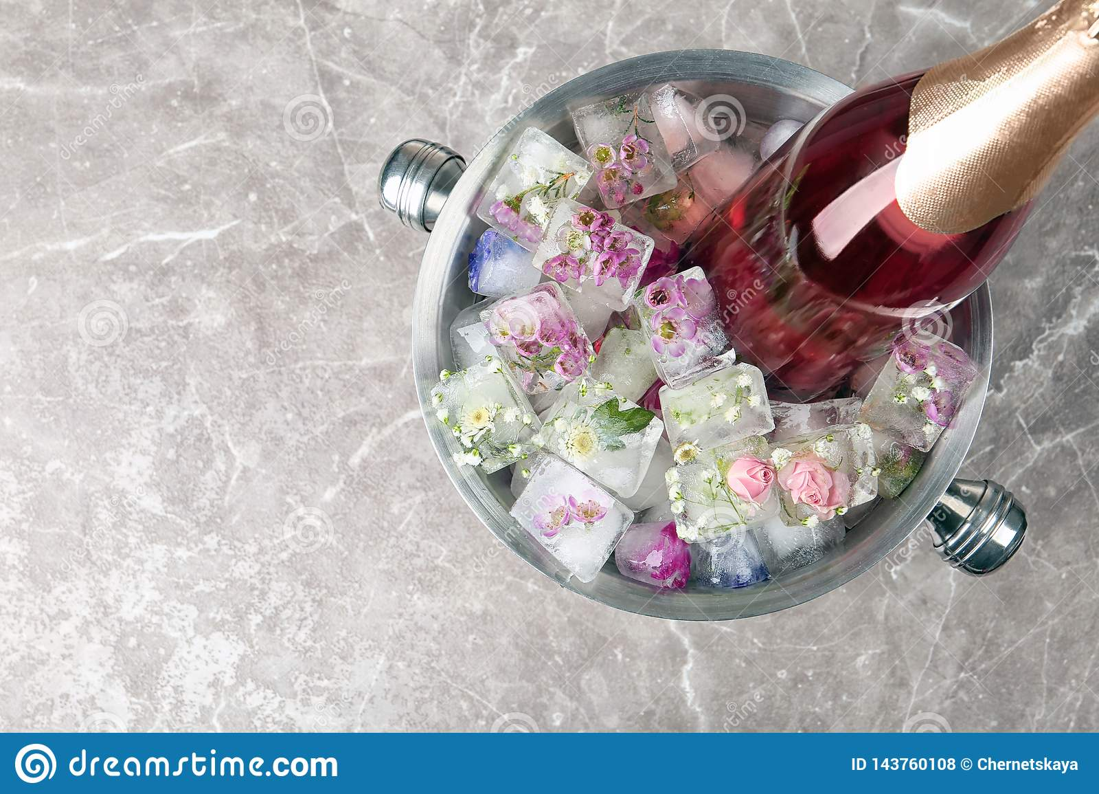 Bottle Of Champagne With Floral Ice Cubes In Bucket On Table Top View Stock Photo Image Of Clear Flowers 143760108