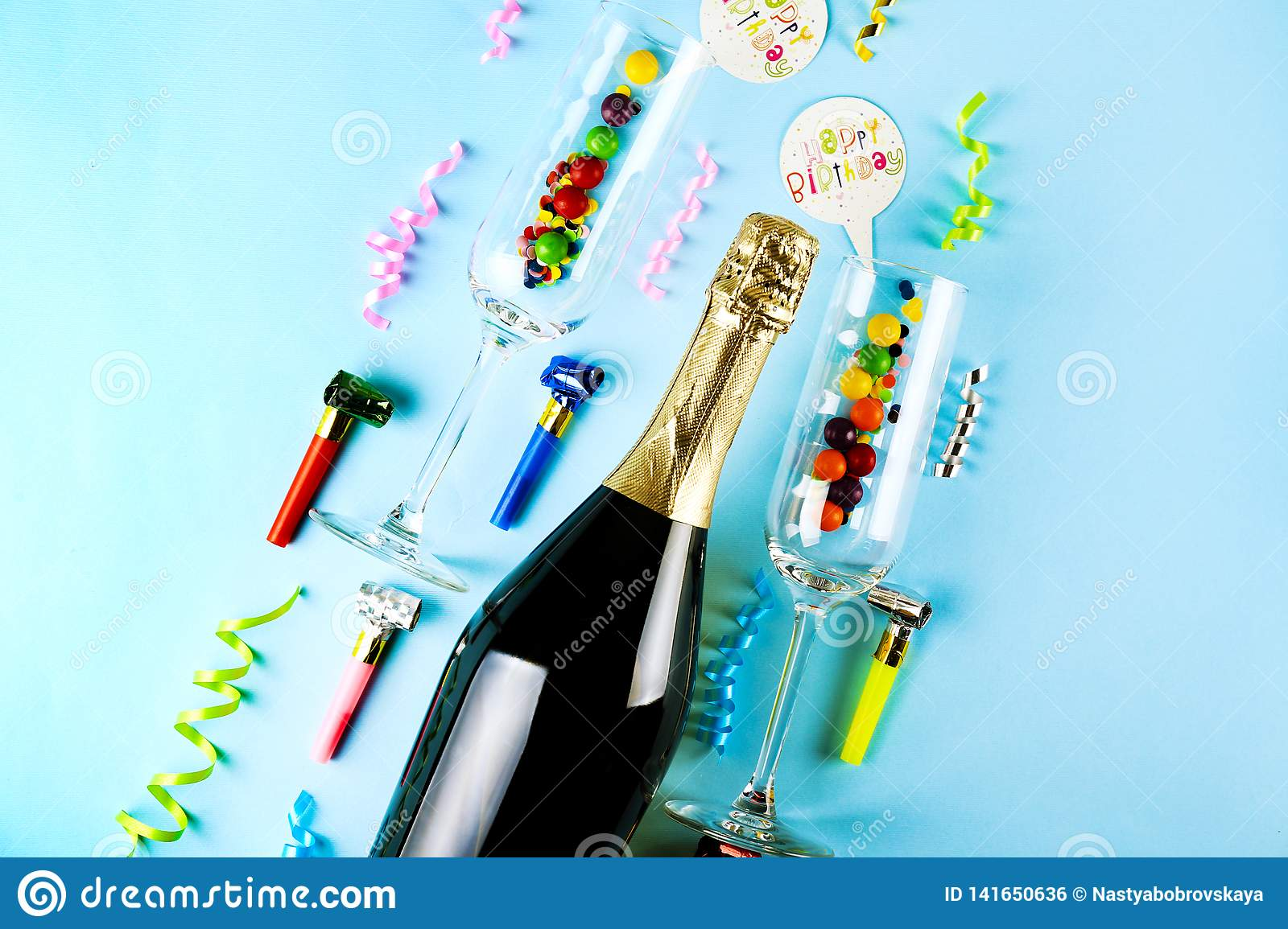 Bottle of champagne, pair of flute glasses, streamers, candles & other party attributes on bright pink paper background. Speech
