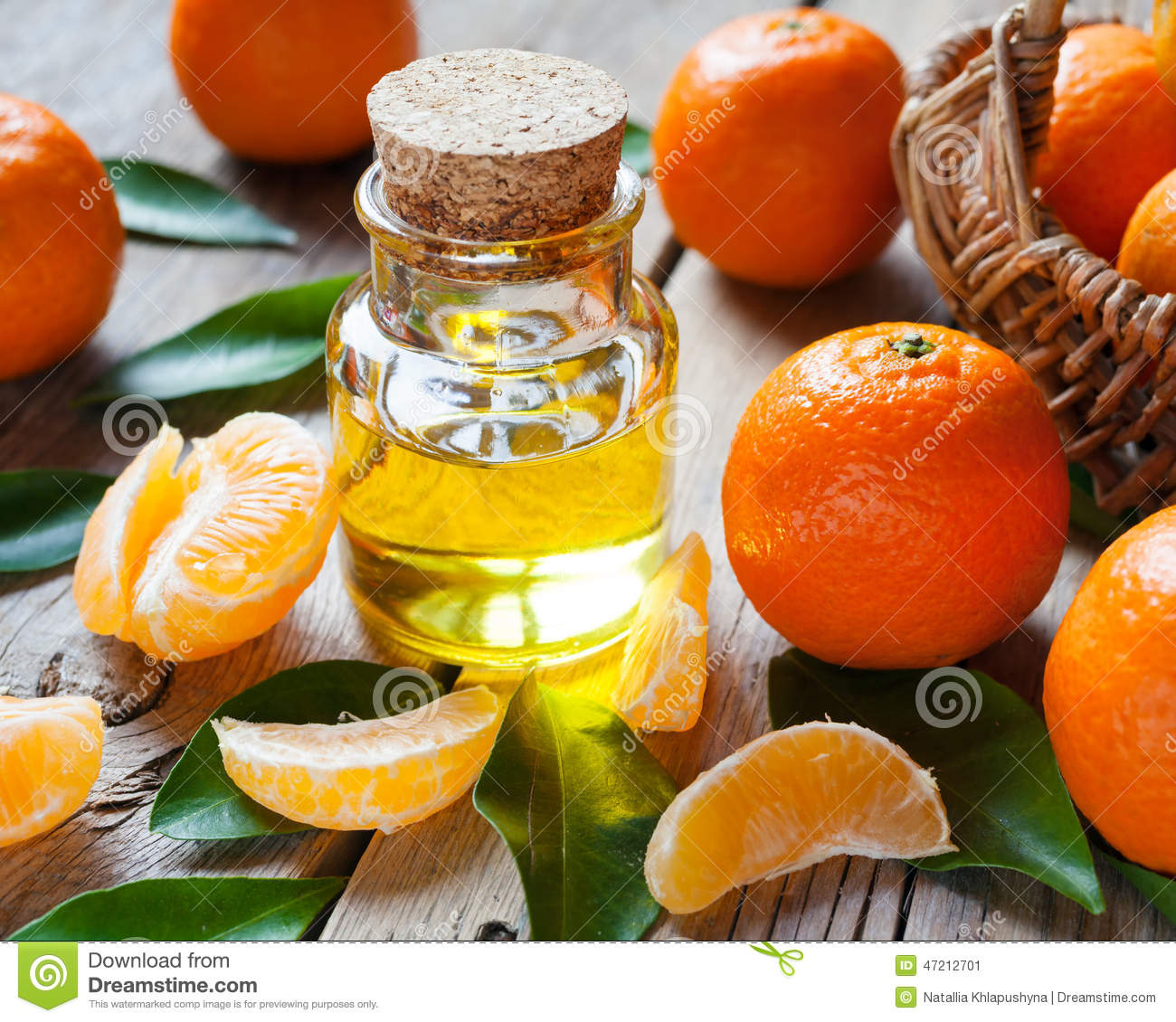 Bottle of essential citrus oil and ripe tangerines with leaves