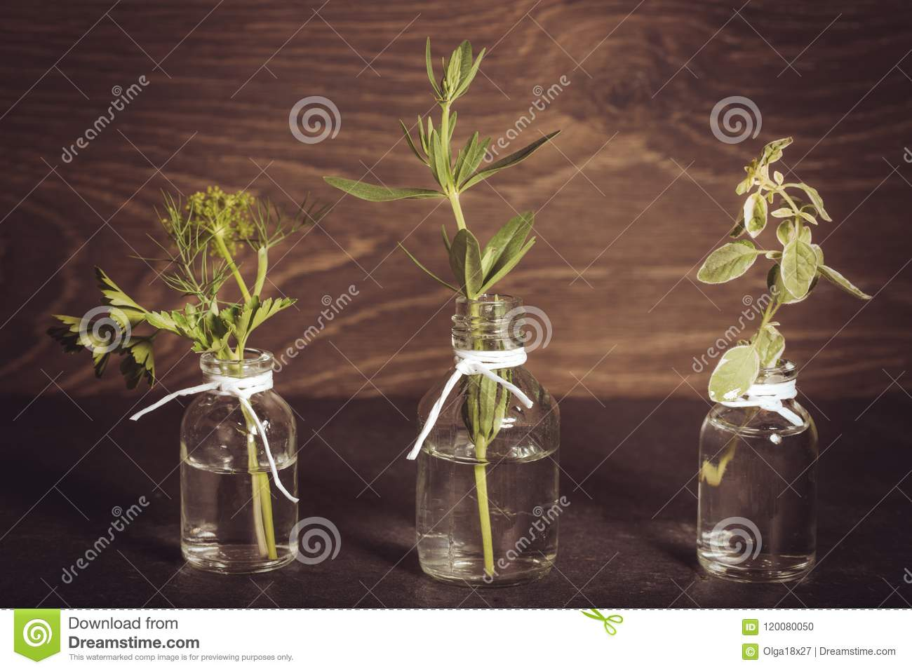 A bottle of essential oil with herbs, parsley, thyme, dill, hyssop, set on an old wooden background. Cooking, alternative medicine