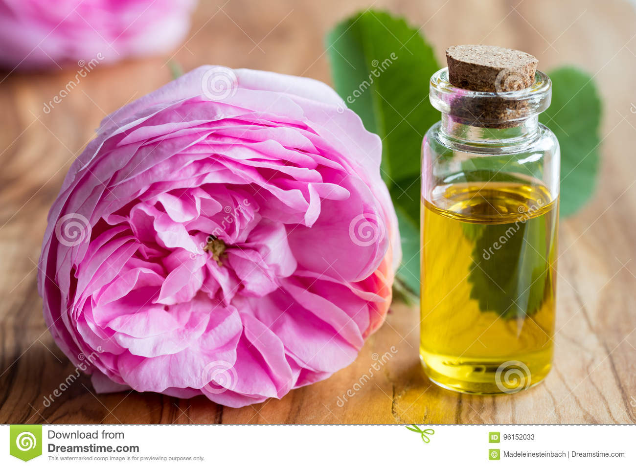 A bottle of essential oil with a rose flower