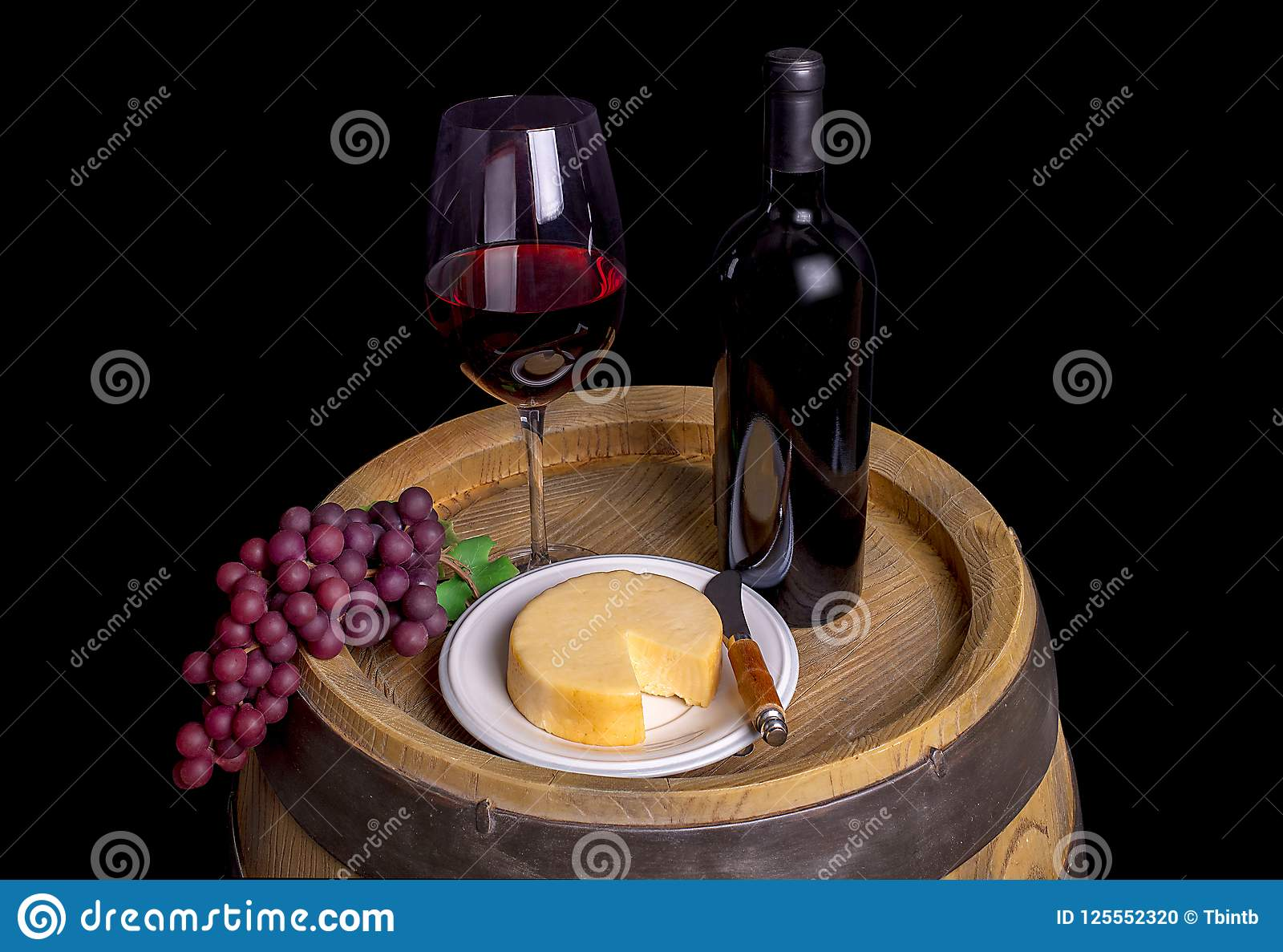 Bottle And Glass Of Red Wine With Grapes And Cheese On Barrel