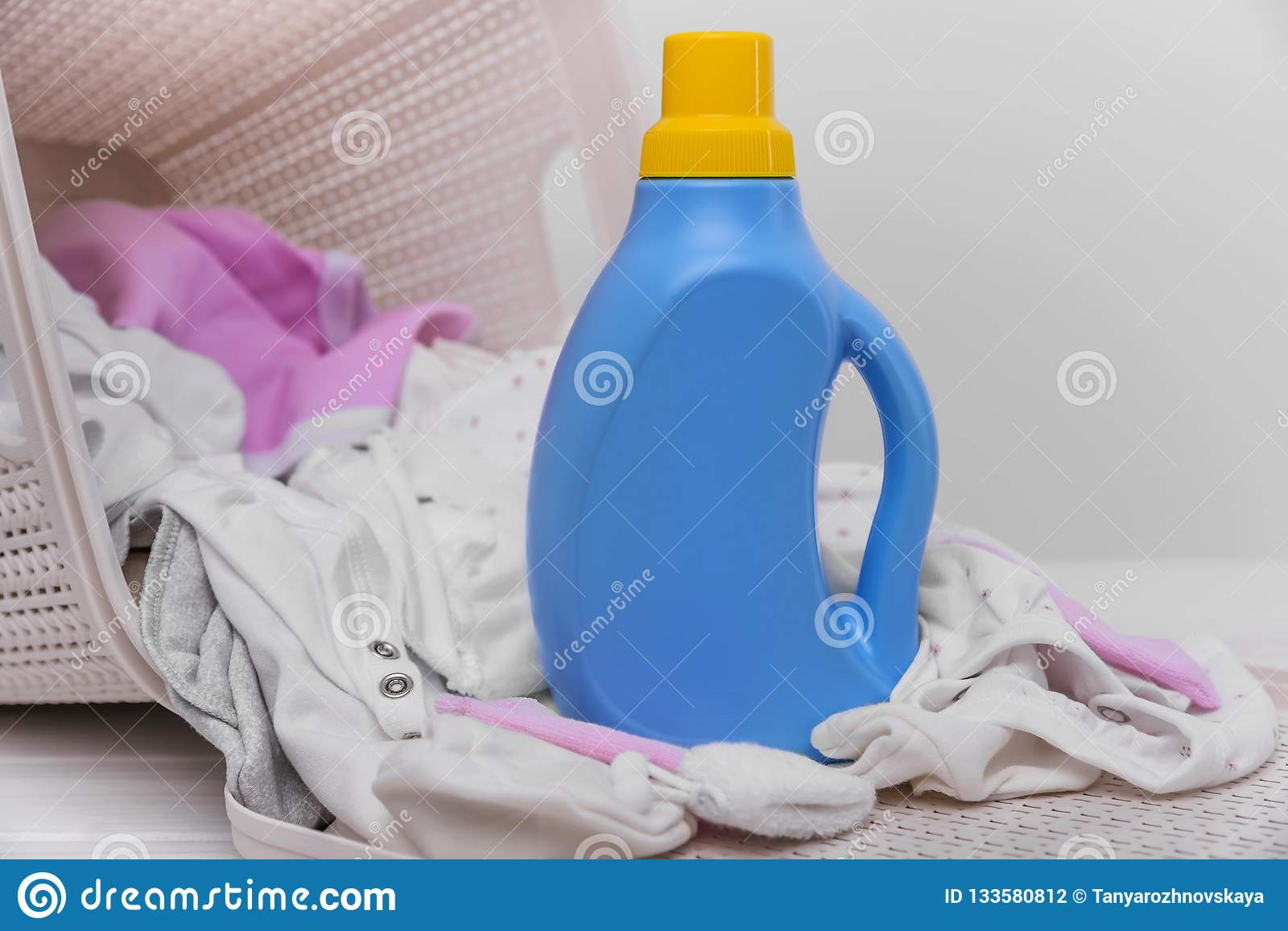 Bottle of laundry detergent in the basket with dirty baby clothes.