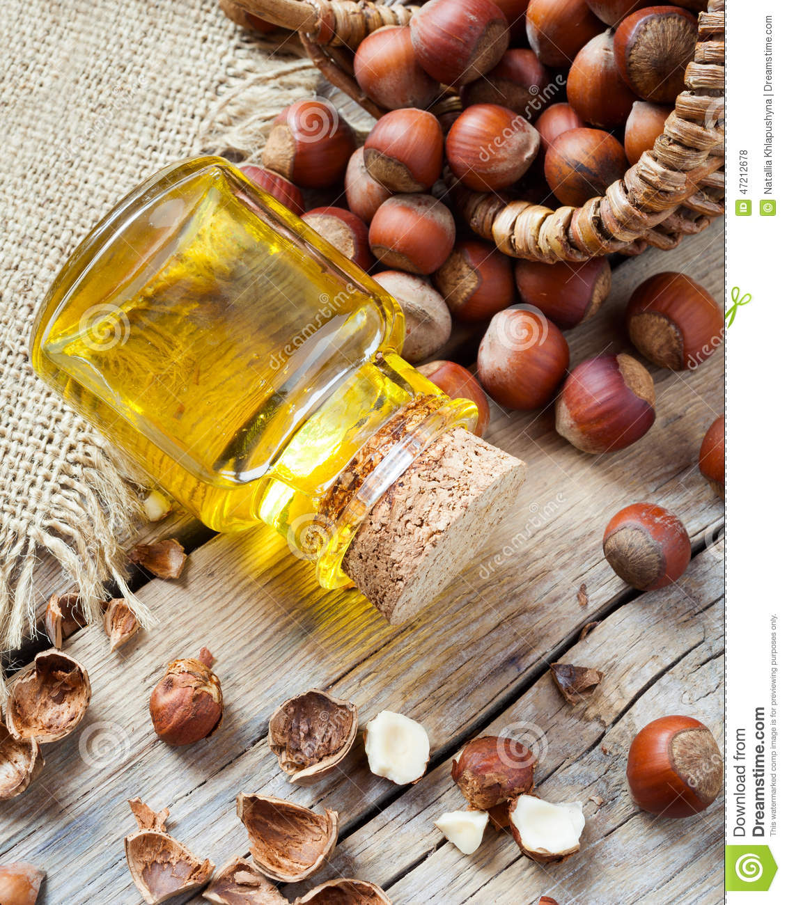 Bottle Of Nut Oil And Basket With Hazelnuts On Old Kitchen