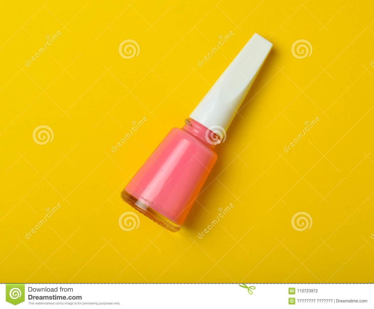 A Bottle Of Pink Nail Polish On A Bright Yellow Background Top View