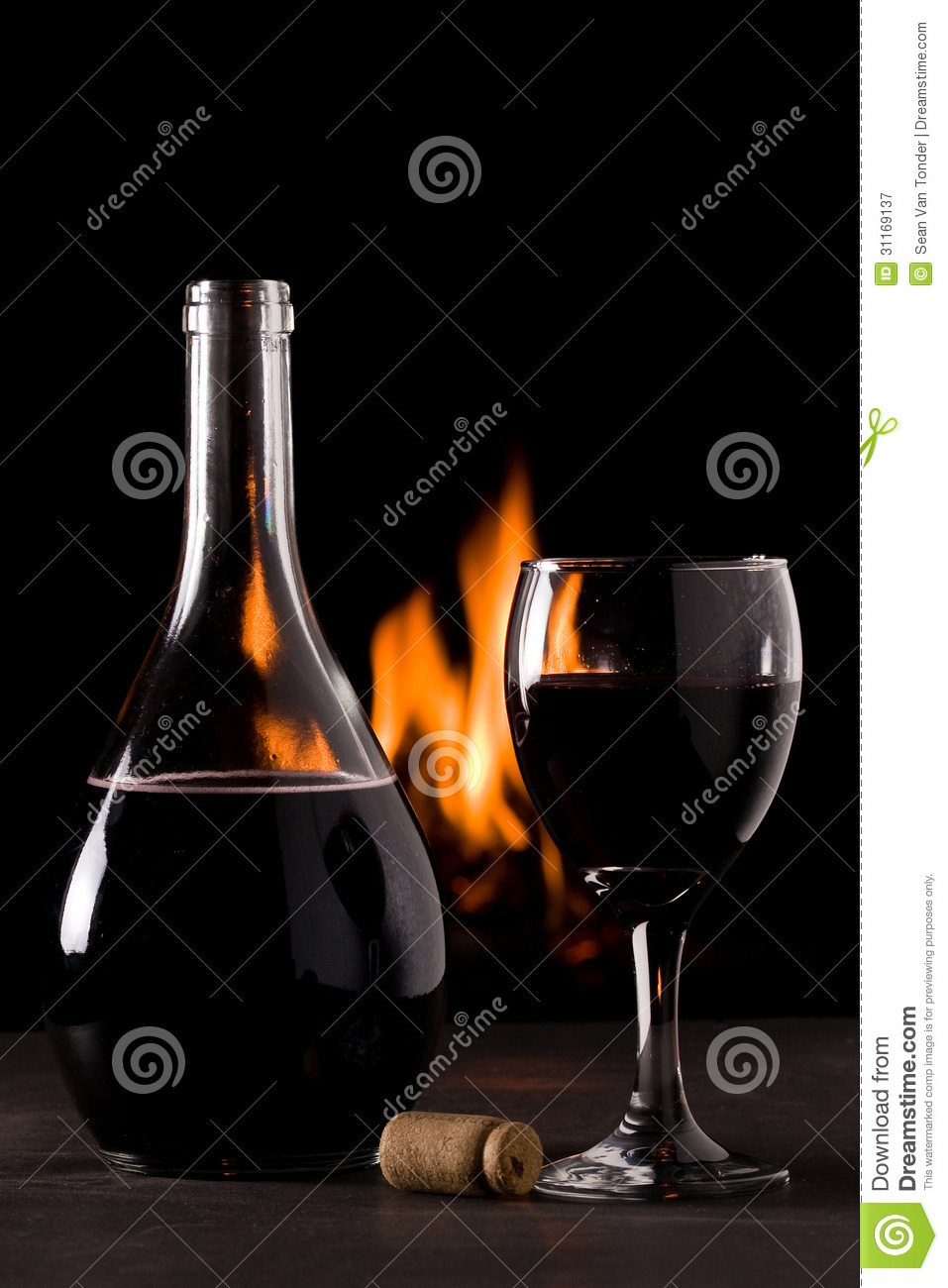 a bottle of red wine and a glass in front of a fireplace royalty