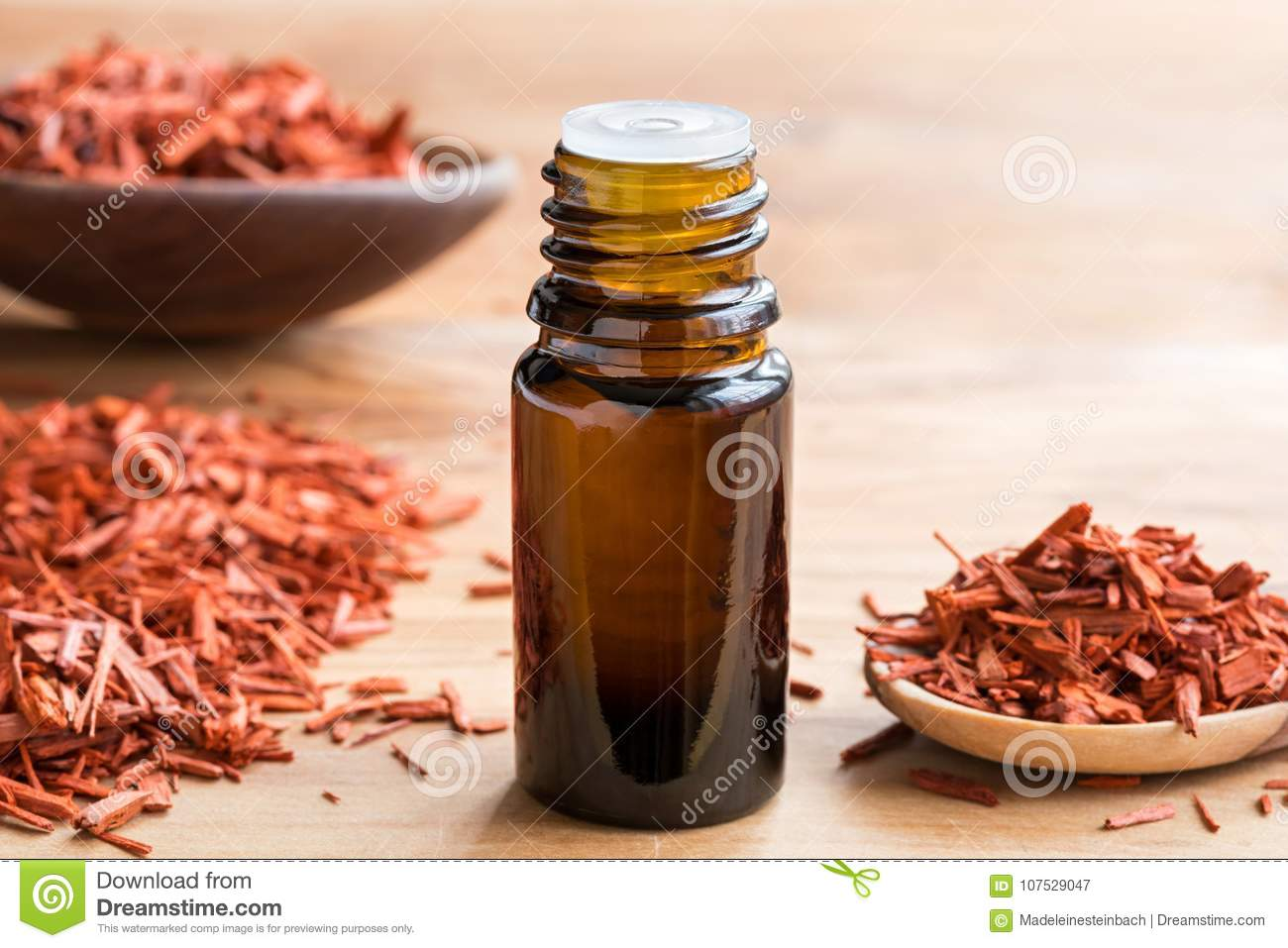Download A Bottle Of Sandalwood Essential Oil With Sandalwood On A Wooden Stock Image - Image of pieces, organic: 107529047