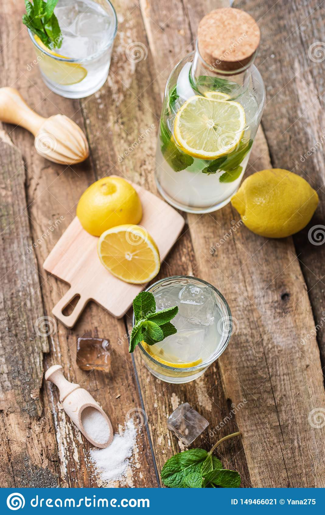 Bottle and two glasses of fresh lemonade with lemon slices, mint and ice on old wooden planks