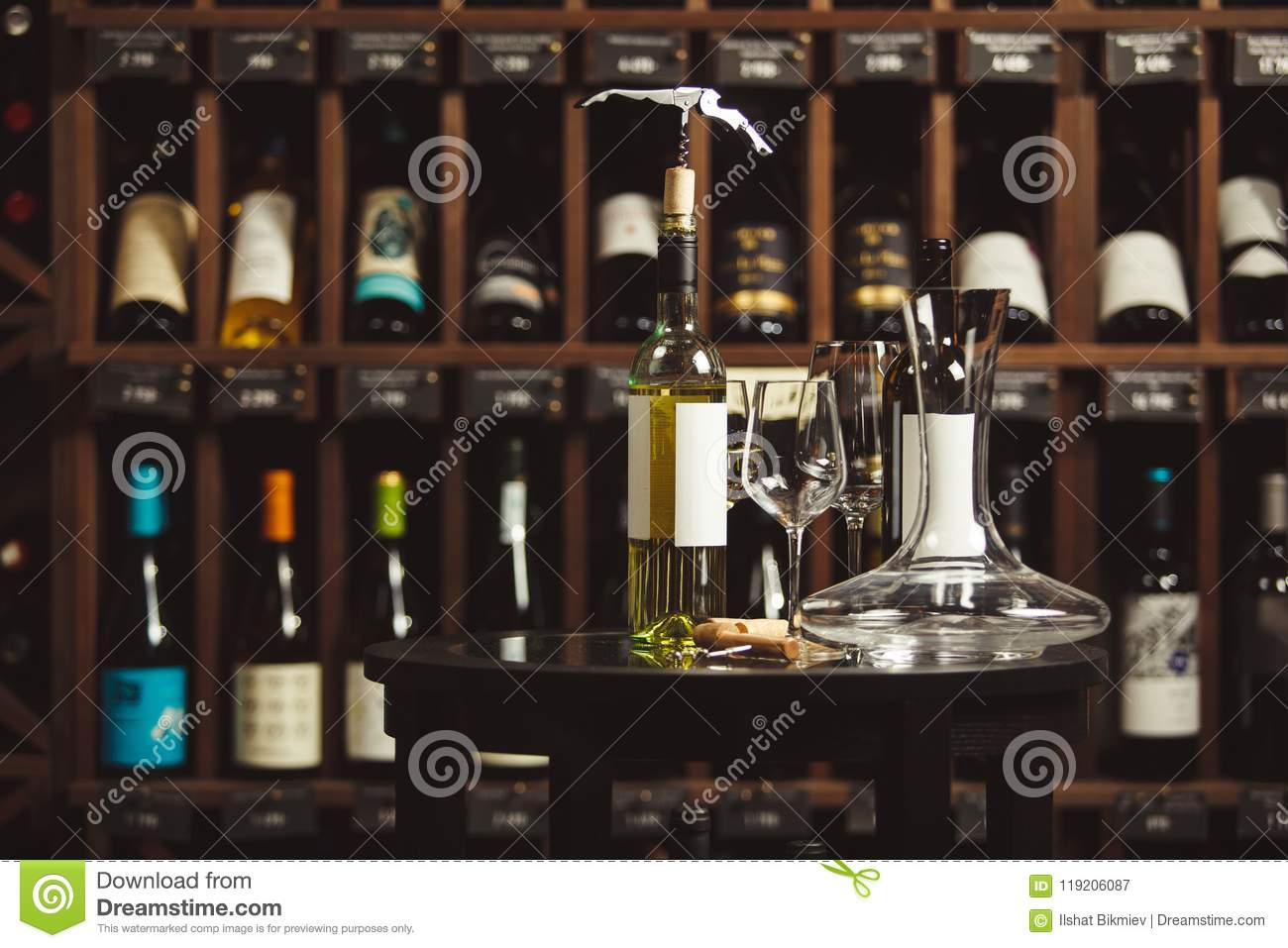 Bottle Of White Wine On The Table Next To Decanter And Glasses Over Shelf  Background.