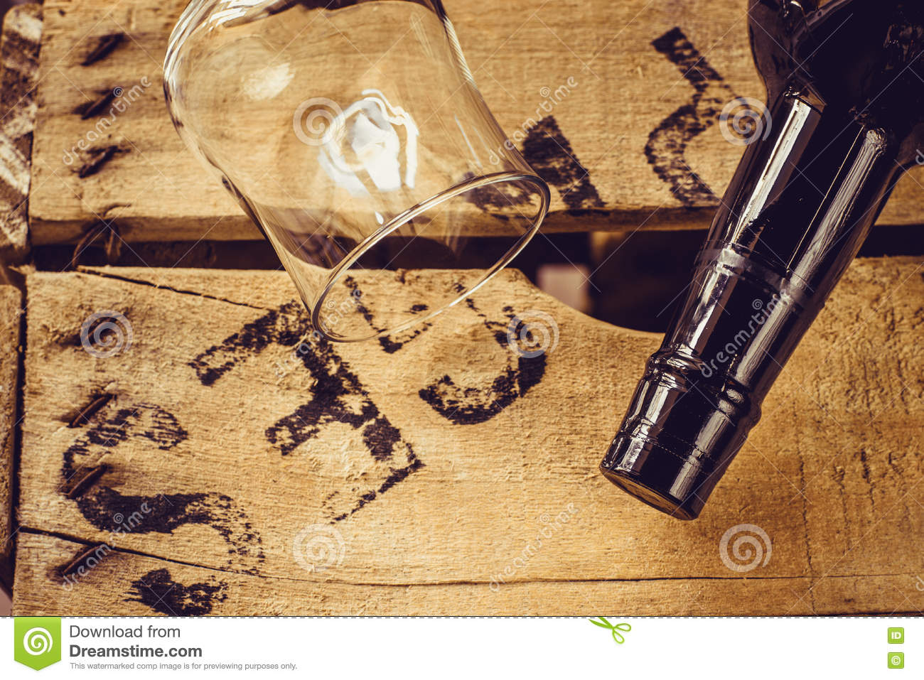 Bottle of wine and an empty wineglass on an aged wood box, top view, selective focus