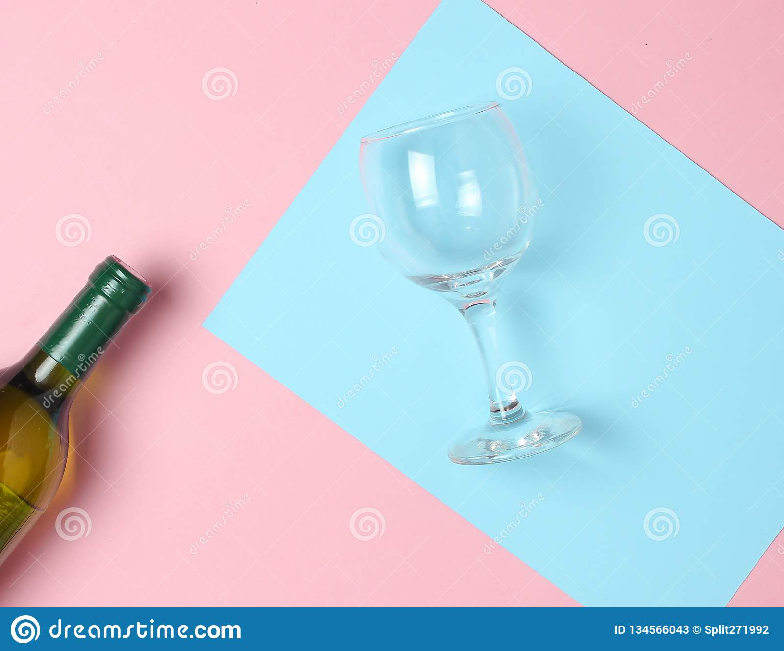 Bottle of wine, glass on a colored pastel background. Top view. Minimalism.