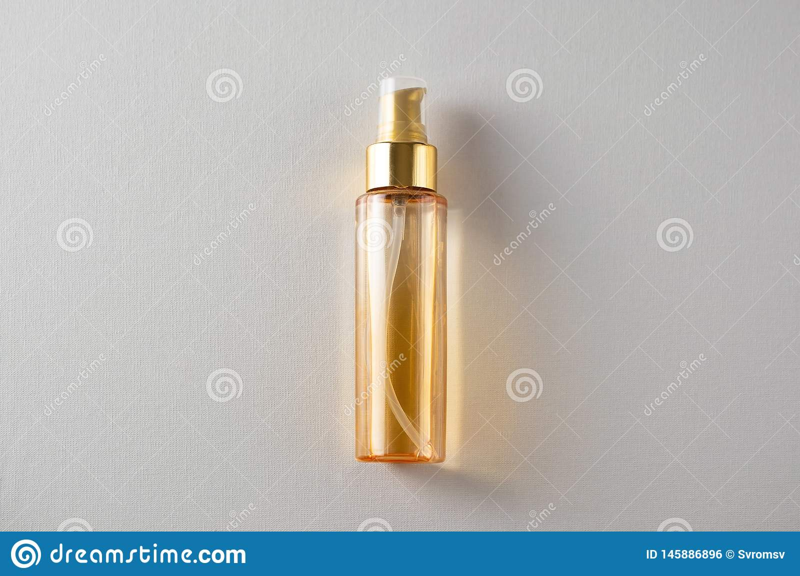 The bottle of yellow cosmetic oil overhead