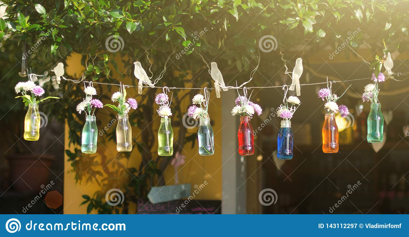 Bottles with colored water and flowers hanging on a string on summer street background