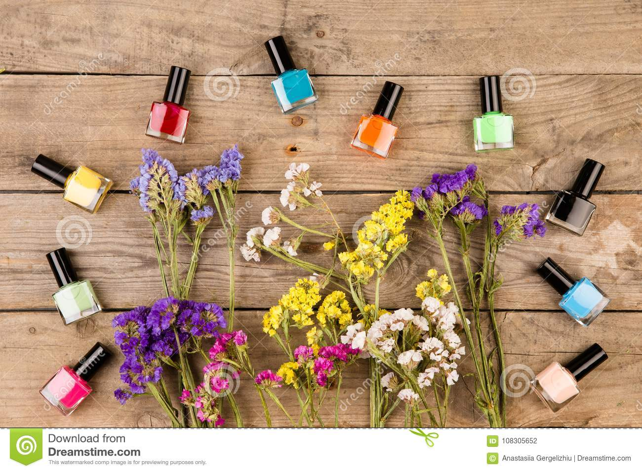 Bottles of nail polish and flowers on brown wooden table stock photo royalty free stock photo izmirmasajfo