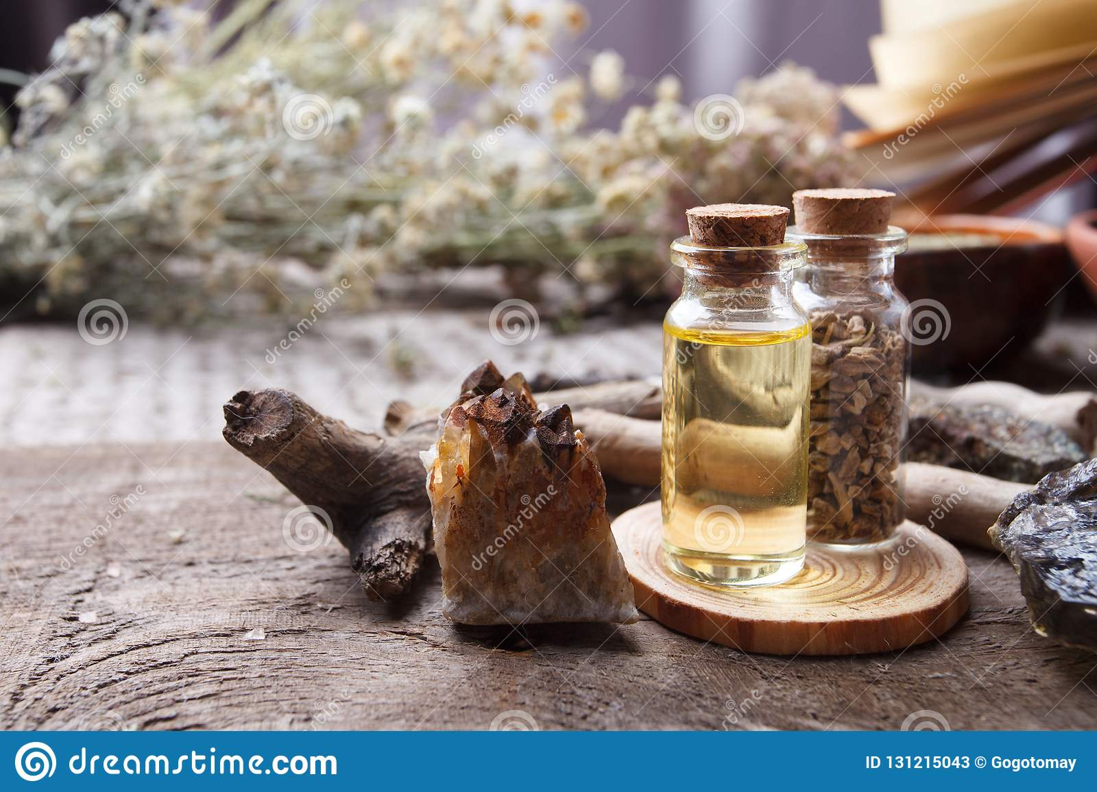 Bottles with herbs, dry flowers, stones and magic objects on witch wooden table. Occult, esoteric, divination and wicca concept