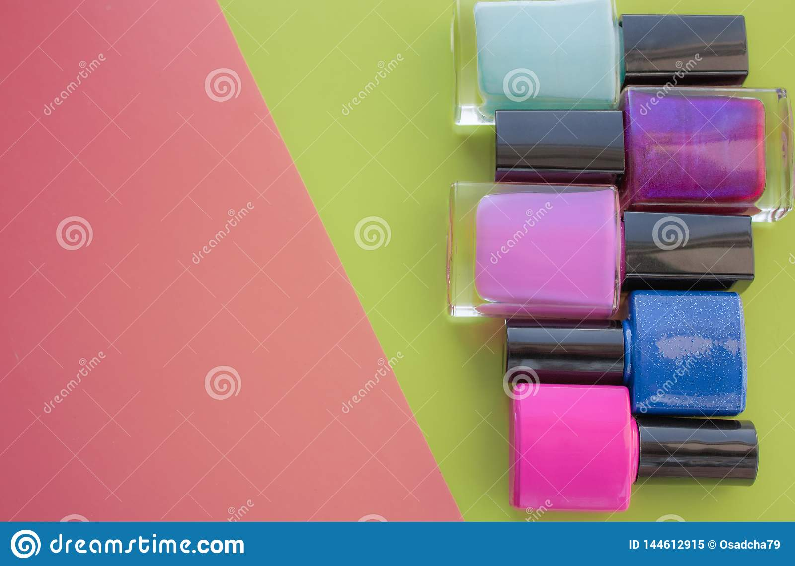 Bottles of nail polish. A group of bright manicures on a pink, green background. With empty space on the left