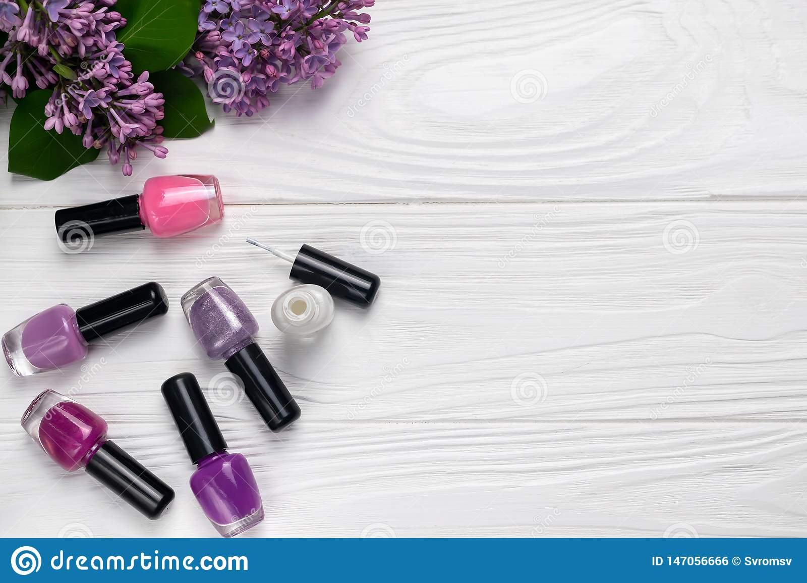 Bottles of nail polish on white wooden background with spring flowers top view with space for text