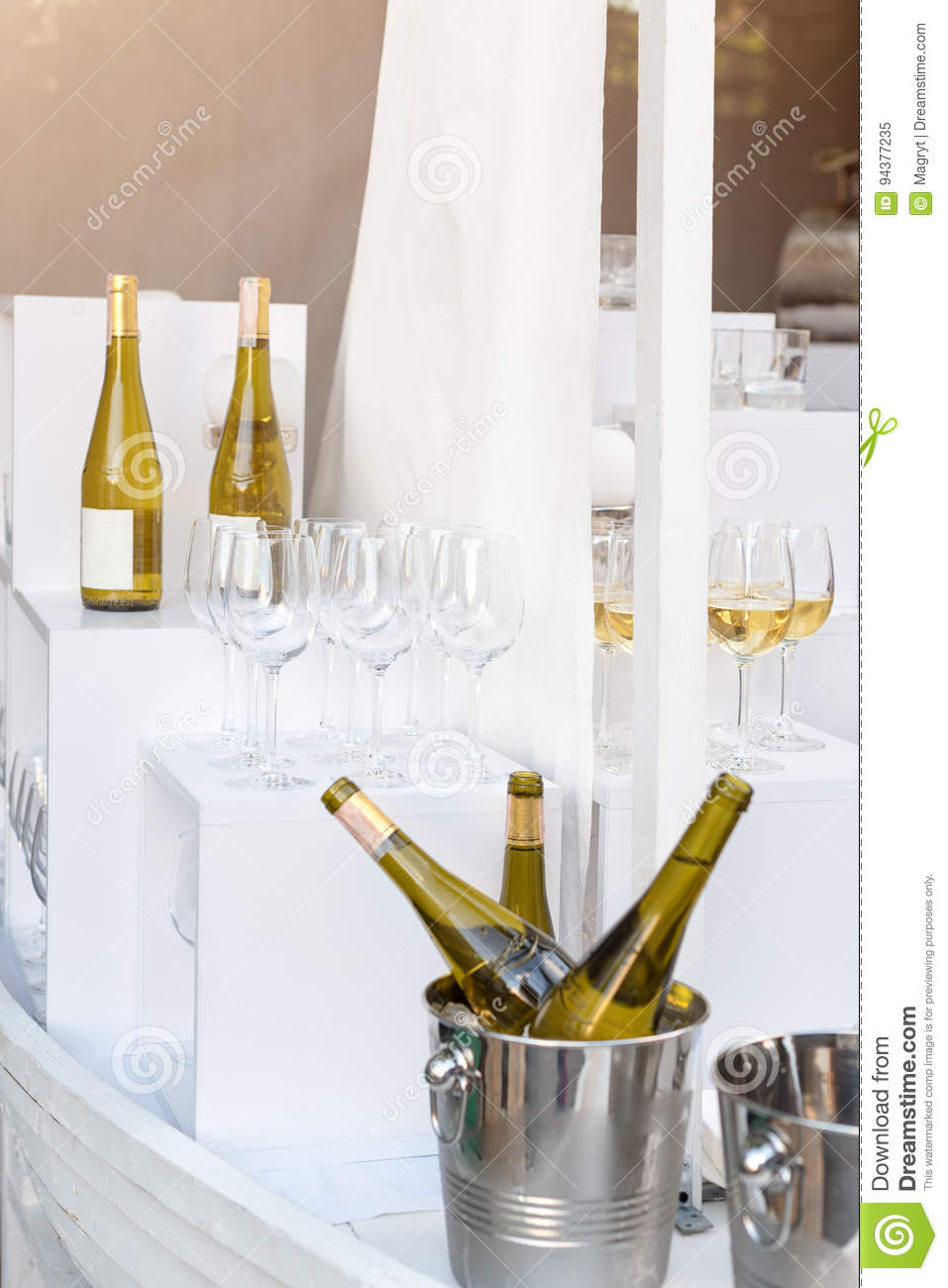 Bottles of white wine standing on serving table. Outdoor party, catering service.