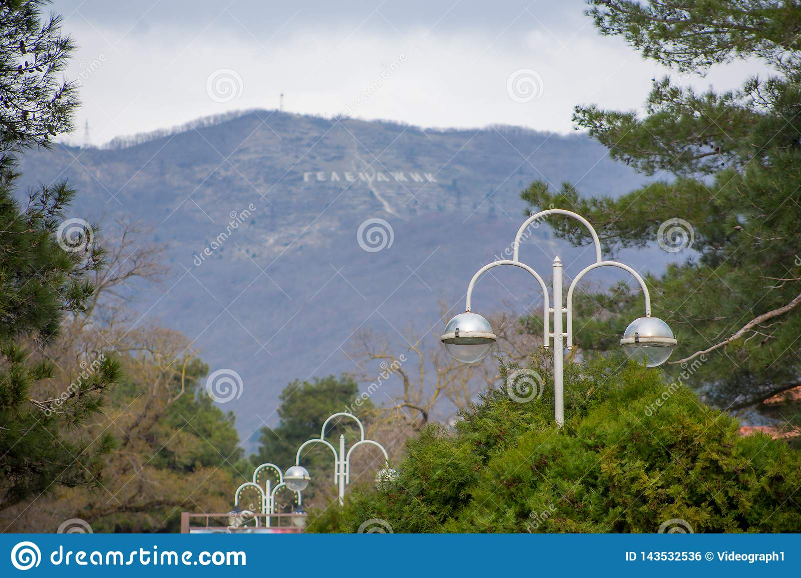 Amazing beautiful view of mountains with inscription `Gelendzhik` from city alley with beautiful lanterns and green trees