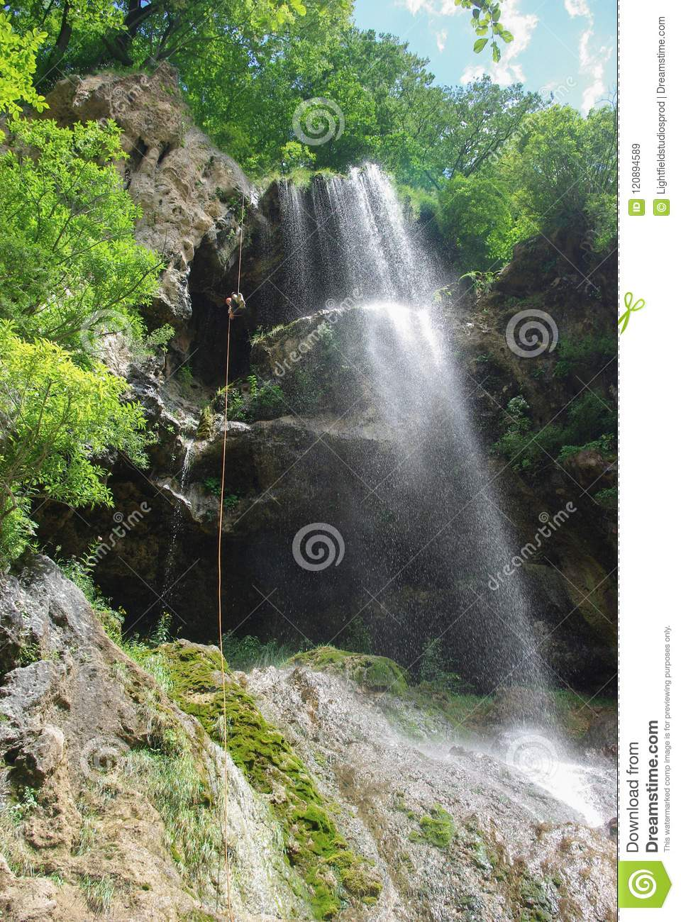 bottom view of man climbing up rope near waterfall, Russian Federation, Caucasus,