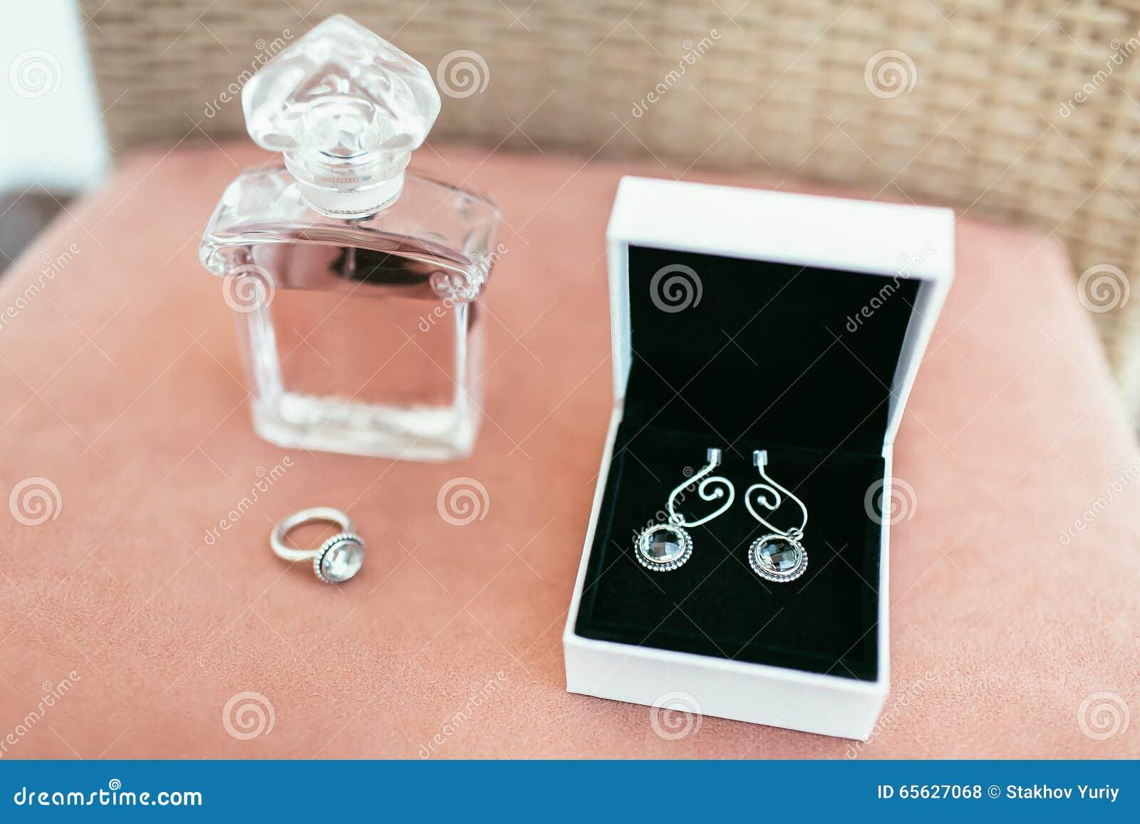 Boucles d oreille de jeune mariée en boîtier blanc et anneau avec le parfum sur épouser le DA