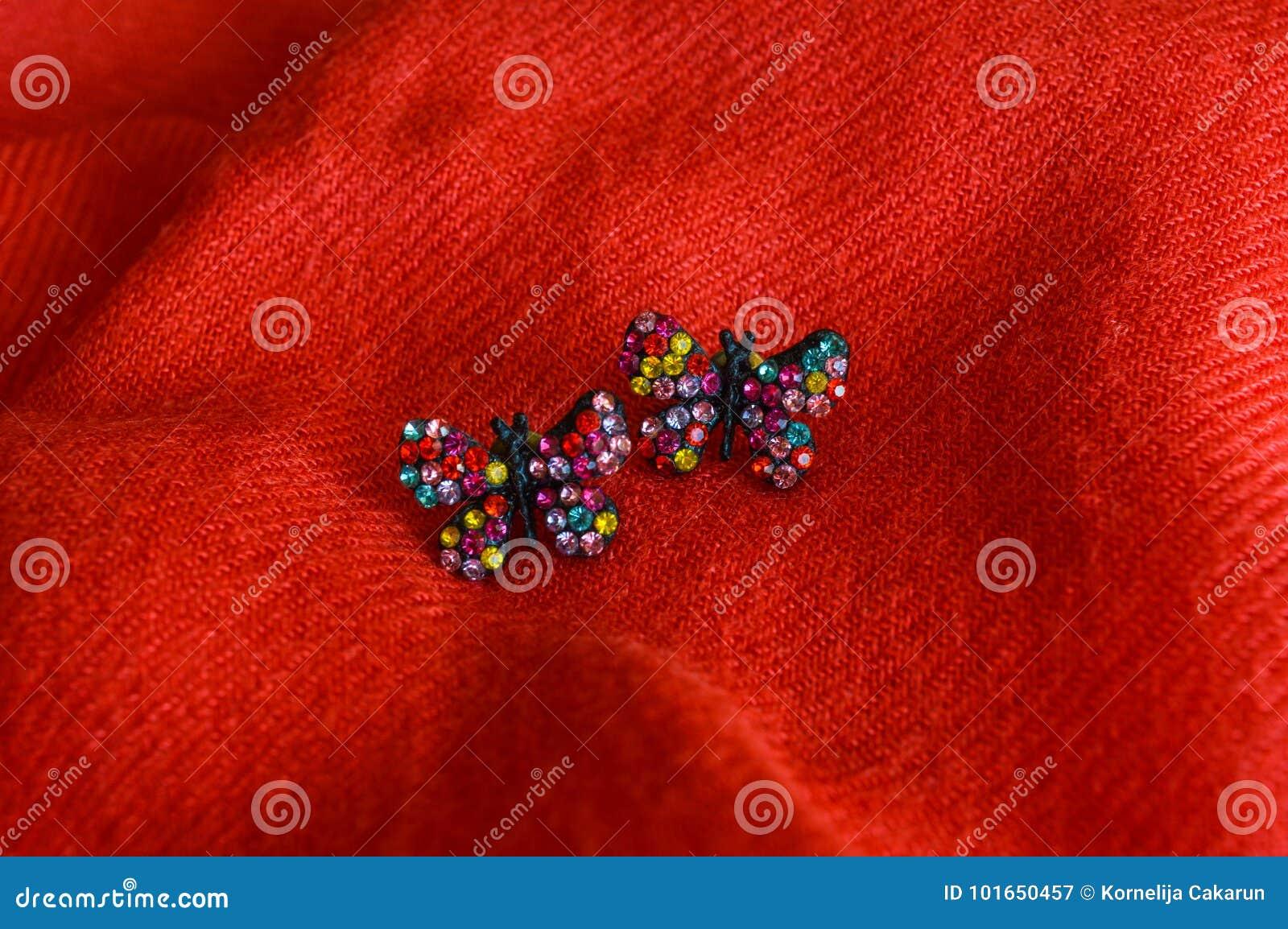 Boucles d oreille faites main colorées, sur le fond rouge de tissu