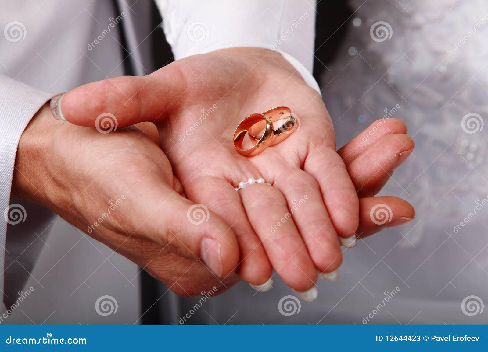 Boucles de mariage sur des mains