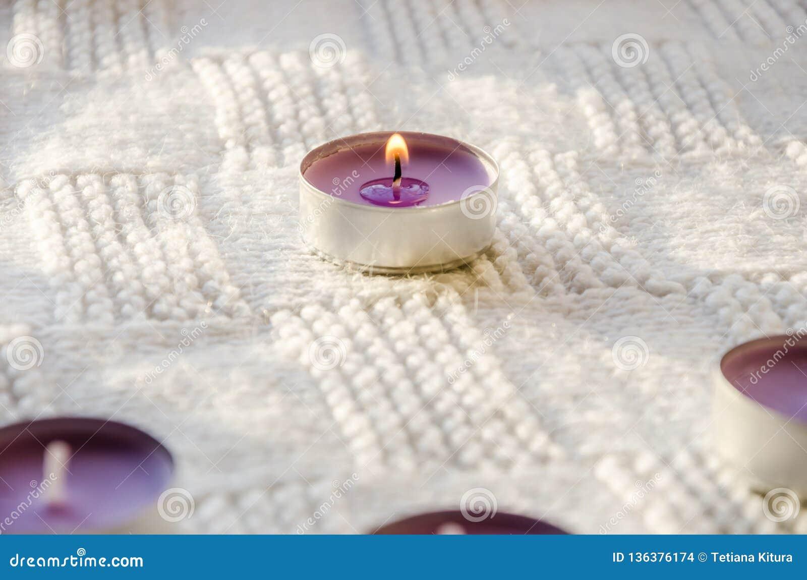 Bougies aromatiques pourpres sur une écharpe