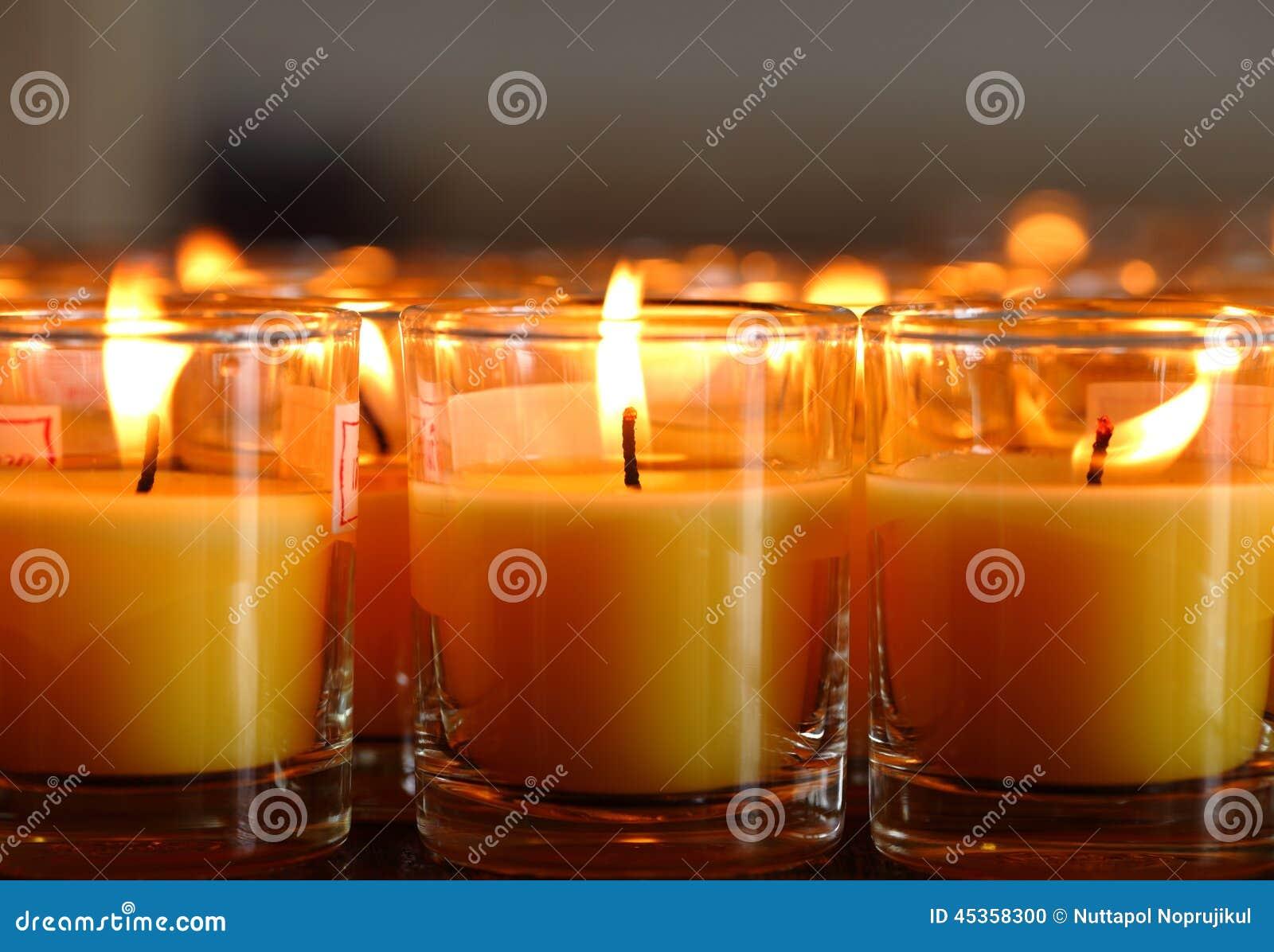 Bougies d église dans des lustres transparents jaunes