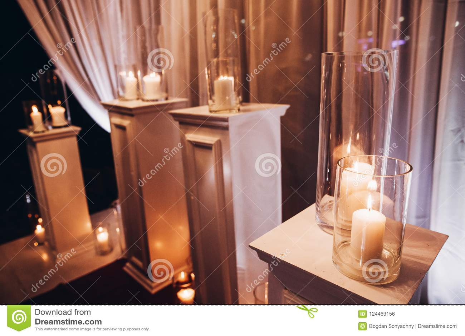 Bougies dans des lanternes en verre et voûte, décor élégant de mariage pour l ev