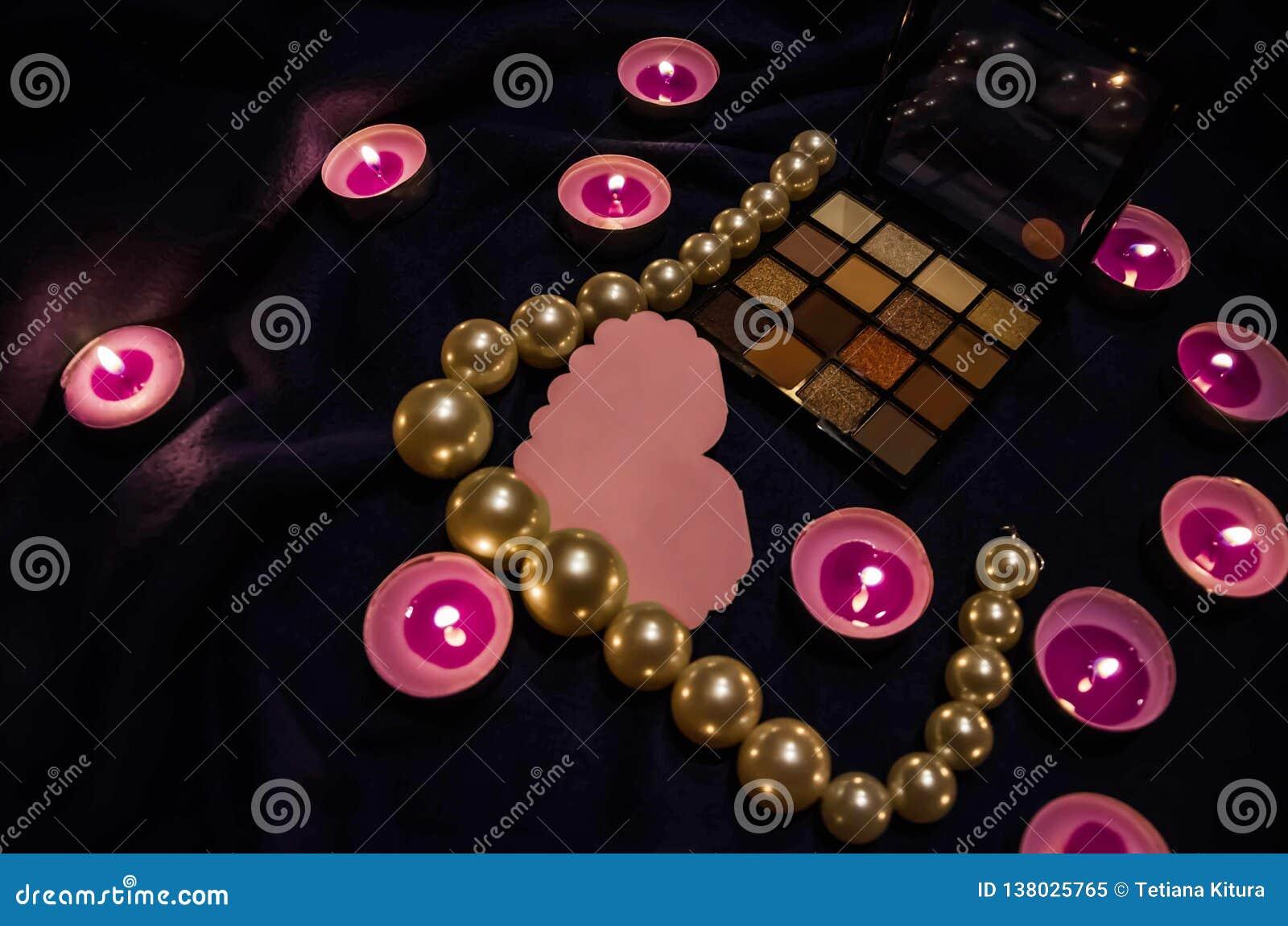Bougies flairées, une palette des ombres, un coeur et belles perles sur une couverture