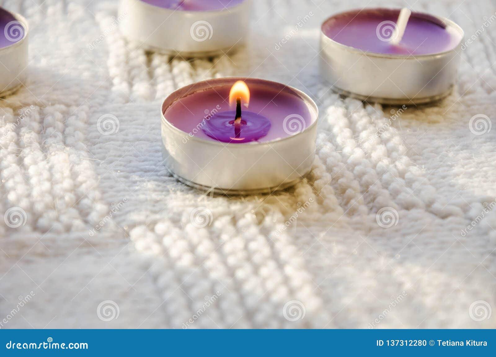 Bougies pourpres et aromatiques sur un fond blanc