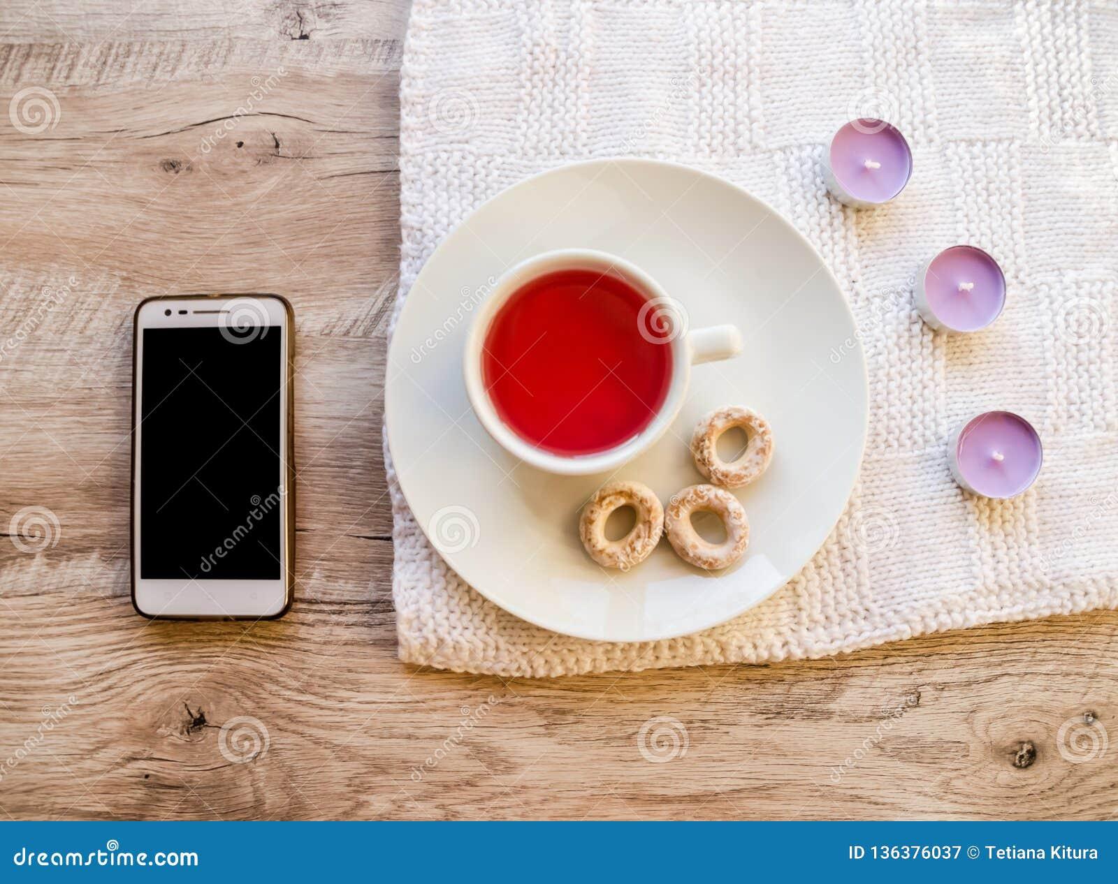 Bougies, tasse, bagels et téléphone aromatiques pourpres sur une table en bois