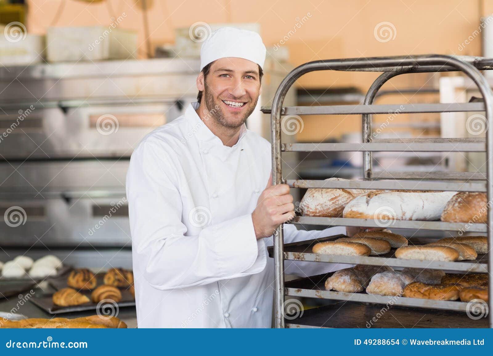 Boulanger de sourire poussant le plateau du pain photo for Cuisine 3d boulanger