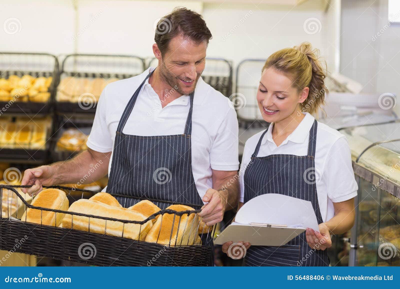 Boulangers de sourire regardant le bloc-notes et tenir un panier avec du pain