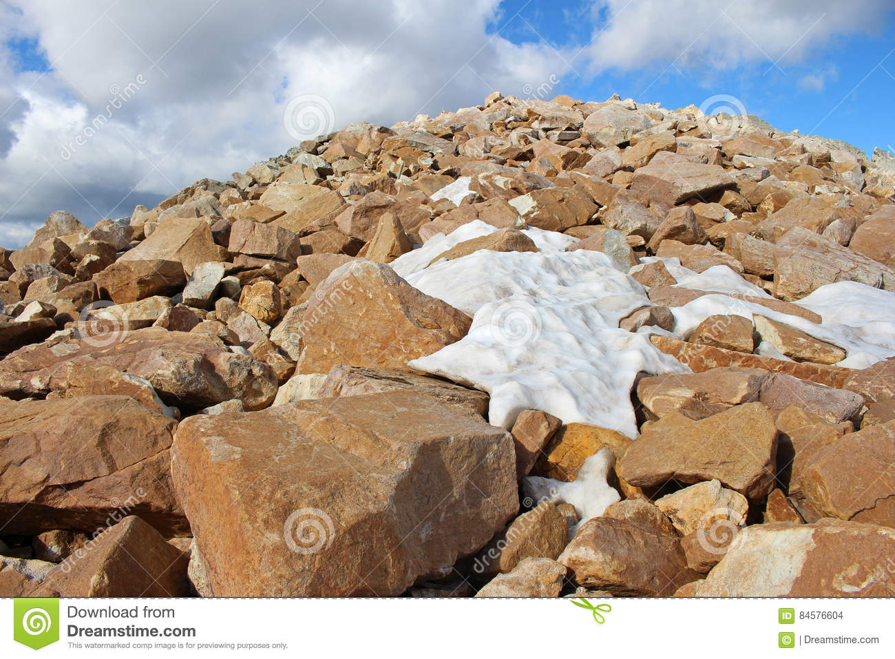 Boulder field near summit of mountain with patchy snow.