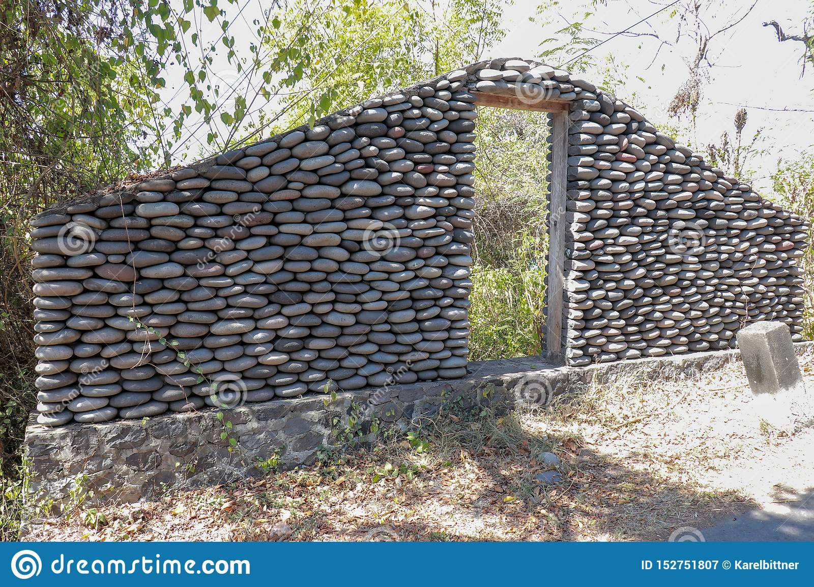 A boulder wall with open wooden doors. Stone wall by the road in Bali Island, Indonesia. Enter the jungle. Mystical place.