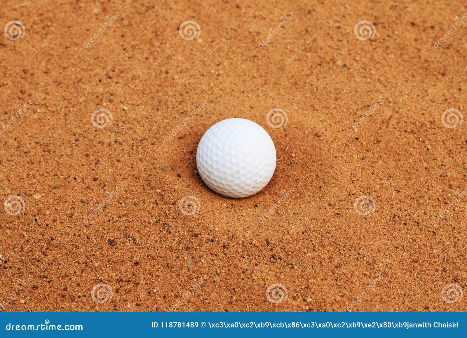 Boule de golf sur le sable rouge