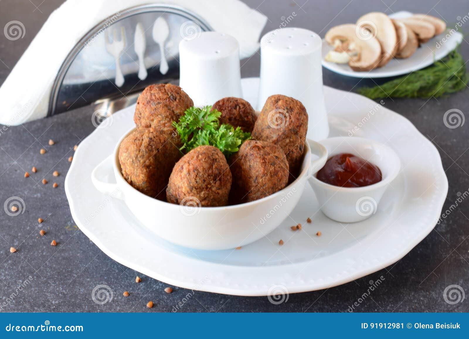 Boules avec du sarrasin et des champignons dans une cuvette blanche sur un fond abstrait gris dieting Aliments de préparation rap