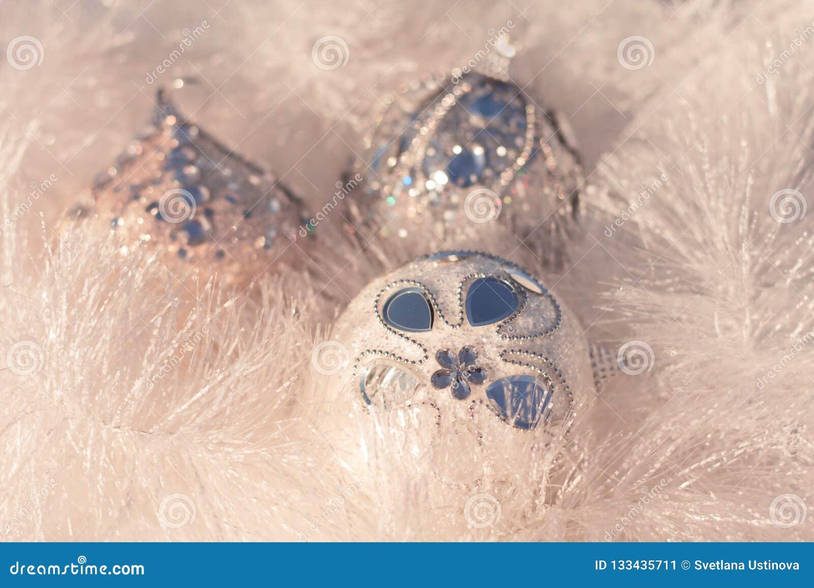 Boules blanches et argentées de Noël sur le fond brillant